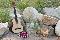 Guitar and shoes in beach sand Stock Photos