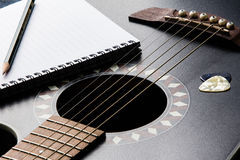 Guitar Song writing. Close up shot of a guitar and pen symbolizing creativity while writing a song Royalty Free Stock Photos