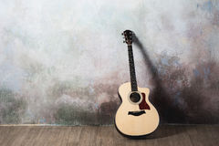 The guitar stands near the wall in the style of grunge, music, musician, hobby, lifestyle, hobby Stock Photography