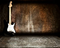 Guitar in steel room. On a grunge background Stock Images