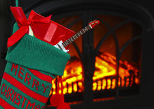 A Guitar in a Stocking at Christmas. An Electric Guitar in a Christmas Stocking Hung by the Fire Royalty Free Stock Photo