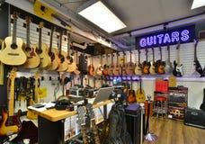 Guitar store full of guitars. Neon guitar store sign in store  full of guitars Stock Images