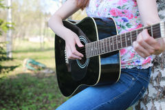 Guitar string woman hand outdoor. Black acoustic guitar in the hands of a talented country music artist Royalty Free Stock Photography