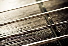 Guitar Strings. A closeup of guitar strings stretched across a fret Royalty Free Stock Image