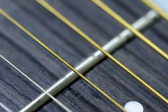 Guitar strings and frets. Close acoustic guitar strings and frets Royalty Free Stock Photography