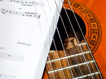Guitar strings and music sheets Stock Photography