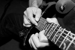 Guitar Tapping. Black-and-white photo of a heavy metal guitarist playing a solo on his Ibanez guitar. Serie of 3 photos royalty free stock photography