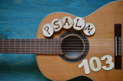 Guitar on teal wood with the word: PSALM 103. Guitar on teal wooden background with wood pieces on it lettering the word: PSALM 103 royalty free stock image
