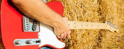 Guitar telecaster in red with a wooden stamp in the hand of a musician background of straw on a sunny summer day royalty free stock photo