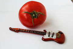 Guitar and tomato Royalty Free Stock Images