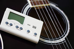 Guitar and tuner for musical instruments Royalty Free Stock Images