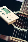 Guitar and tuner for musical instruments Royalty Free Stock Photography
