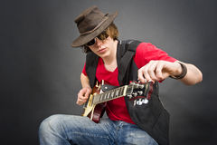 Guitar Tuning. A musician wearing an old leather hat tuning his guitar Royalty Free Stock Images