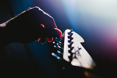Guitar tuning . Hand rotating knob for tuning a guitar string Stock Photography