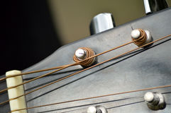 Guitar tuning pegs and posts on guitar head, macro. Closeup of the tuning mechanisms of an acoustical, steel-stringed guitar Royalty Free Stock Image