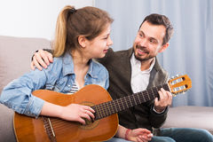 Guitar tutor helping client learn instrument. Happy young guitar tutor helping teenage to learn instrument stock photo