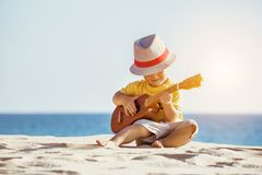 Guitar ukulele concept with little boy at the beach. Musical concept with little boy playing ukulele at sunny sea beach Stock Image