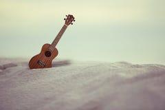Guitar ukulele on sand beach Stock Photos