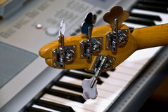 Guitar and upright electro-piano. Four pegs of bass-guitar on a background the keys of upright electro-piano Stock Photo