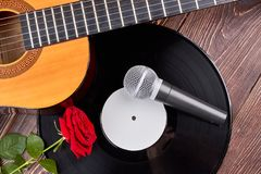 Guitar, vinyl record, microphone and rose. stock photo