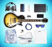 Guitar and wear and accessories on blue background Stock Photos