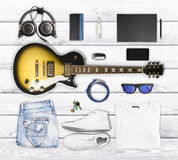 Guitar and wear and accessories on a wooden surface Royalty Free Stock Photography