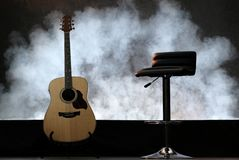 Guitar with white smoke on the black floor. With chair. stock photography