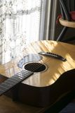 Guitar by Window. Acoustic guitar reflecting the lace window drapery, evoking classical music Royalty Free Stock Image