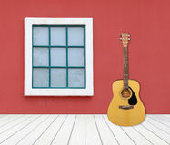 Guitar with window on cement wall Royalty Free Stock Image
