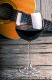 Guitar and Wine on a wood table Royalty Free Stock Photos