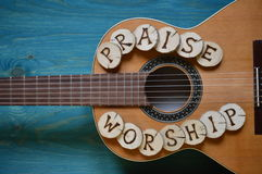 Guitar on wood with words: PRAISE and WORSHIP. Guitar on teal wooden background with wood pieces on it lettering the words: PRAISE and WORSHIP stock photo