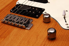 A guitar with wooden body. A guitar chrome bridge with wooden body and knobs Royalty Free Stock Photos