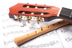 Guitar and wooden flute. On sheet music. Close up Stock Photo