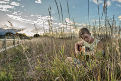 Guitar. Young man playing guitar in a grass field Royalty Free Stock Photo