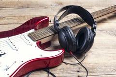 Guitare électrique avec des écouteurs sur la table en bois Image stock