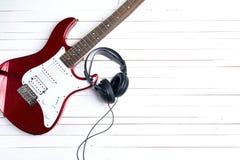 Guitare électrique avec des écouteurs sur la table en bois blanche Copiez Spac Image libre de droits