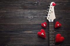 Guitare électrique de cou avec des coeurs sur un fond en bois foncé PS Photo stock