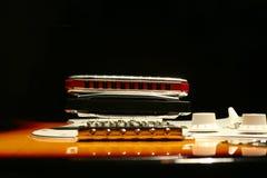 Guitare électrique de vintage avec l'harmonica sur le fond noir Photos stock