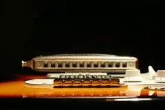 Guitare électrique de vintage avec l'harmonica sur le fond noir Images libres de droits