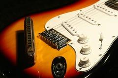 Guitare électrique de vintage avec l'harmonica sur le fond noir Images stock