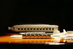 Guitare électrique de vintage avec l'harmonica sur le fond noir Image stock