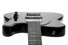 Guitare électrique noire sur un fond blanc Images libres de droits