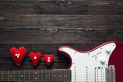 Guitare électrique rouge avec des coeurs sur un fond en bois foncé Station thermale Image stock