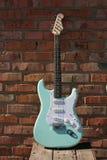 Guitare électrique sur un mur de briques Image libre de droits