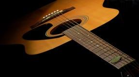 Guitare acoustique dans l'obscurité Images libres de droits