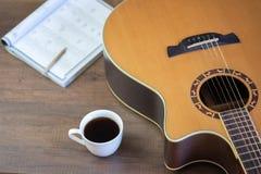 Guitare acoustique et écrire les notes musicales et la tasse de café images stock