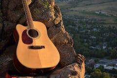 Guitare acoustique lumineuse dans les montagnes Photographie stock libre de droits