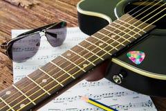 Guitare acoustique, lunettes de soleil et notes musicales de feuille sur la table Images libres de droits