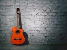 Guitare acoustique se penchant sur le mur sale Photographie stock