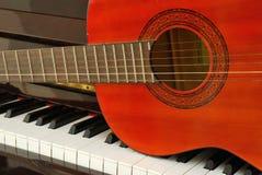Guitare acoustique sur le clavier de piano Photo stock